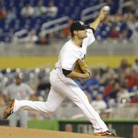 Photo - Miami Marlins starting pitcher Brad Hand throws during the first inning of the MLB National League  baseball game against the Washington Nationals, Monday, April 14, 2014, in Miami. (AP Photo/Lynne Sladky)