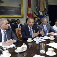 Photo - President Barack Obama, flanked by Attorney Holder Eric Holder, left, and Housing and Urban Development Secretary Shaun Donovan, left, speaks about a report from