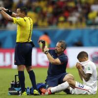 Photo - United States' Fabian Johnson, right, receives treatment during the World Cup round of 16 soccer match between Belgium and the USA at the Arena Fonte Nova in Salvador, Brazil, Tuesday, July 1, 2014. (AP Photo/Julio Cortez)