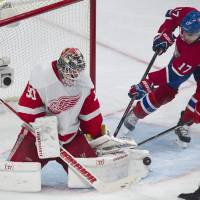 Photo - Detroit Red Wings goaltender Jonas Gustavsson is scored on by Montreal Canadiens' Brian Gionta (not shown) as Canadiens' Rene Bourque looks for a rebound during the third period of an NHL hockey game in Montreal, Saturday, April 5, 2014. (AP Photo/The Canadian Press, Graham Hughes)