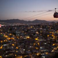 Photo - In this May 10, 2013 photo, homes are lit at night as cable-cars move commuters over the Complexo do Alemao complex of shantytowns in Rio de Janeiro, Brazil.  The cable-car system linking six of its hilltops over a 3.5-kilometer (2.3-mile) route has become a popular tourist attraction. (AP Photo/Felipe Dana)