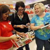 Photo -   IMAGE DISTRIBUTED FOR TARGET - Target team member Melba Breidenstein assists Angela McCrary and Rebecca Freeman during Black Friday shopping on Thursday, November 22, 2012 in Hurst, Texas. (Richard W. Rodriguez/AP Images for Target)