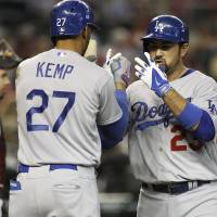Photo - Los Angeles Dodgers' Adrian Gonzalez, right, is greeted at home plate by teammate Matt Kemp (27) after hitting a three-run home run against the Arizona Diamondbacks during the third inning of a baseball game on Sunday, April 13, 2014, in Phoenix. (AP Photo/Ralph Freso)