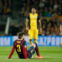 Photo - Barcelona's Gerard Pique sits on the pitch after injuring himself during a first leg quarterfinal Champions League soccer match between Barcelona and Atletico Madrid at the Camp Nou stadium in Barcelona, Spain, Tuesday April 1, 2014. Pique had to be substituted. (AP Photo/Emilio Morenatti)