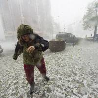 Photo - A pedestrian runs for safety as a hail storm hits downtown Colorado Springs, Colo., Wednesday, May 21, 2014. (AP Photo/The Gazette, Christian Murdock) MAGAZINES OUT.