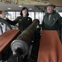 "Photo - Saratoga National Historical Park Curator Christine Valosin, left, and superintendent Joe Finan pose with a Revolutionary War cannon after a ceremony for the cannon at the park on Friday, Nov. 15, 2013, in Stillwater, N.Y. The cannon surrendered by the British after the Battles at Saratoga is back ""home"" after stints in museums and private collections in four states over the past half-century. Officials at Saratoga say the rare Revolutionary War cannon was tracked down to Alabama's Tuscaloosa Museum of Art and recently delivered to the park, located 20 miles north of Albany. (AP Photo/Mike Groll)"