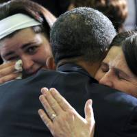 Photo - President Barack Obama hugs Newtown, Conn., family members after speaking at the University of Hartford in Hartford, Conn., Monday, April 8, 2013. Obama said that lawmakers have an obligation to the children killed and other victims of gun violence to act on his proposals.  (AP Photo/Susan Walsh)