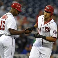Photo -   Washington Nationals' Ian Desmond, right, receives congratulations from his third base coach Bo Porter after hitting a two-run home run in the first inning of their baseball game against the Chicago Cubs at Nationals Park, Tuesday, Sept. 4, 2012, in Washington. (AP Photo/Richard Lipski)