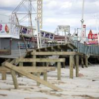 Photo - FILE - In this Oct. 31, 2012 file photo, the Seaside Heights boardwalk is heavily damaged after Superstorm Sandy moved through the area. The iconic boardwalk where generations of families and teens got their first taste of the Jersey Shore and where the reality show of the same name was filmed is being rebuilt following its destruction in Superstorm Sandy. Seaside Heights on Wednesday, Jan. 16, 2013 awarded a $3.6 million contract to have the boardwalk rebuilt in time for Memorial Day weekend. (AP Photo/The Star-Ledger, David Gard, Pool, File)