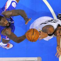 Photo -   San Antonio Spurs forward Tim Duncan, right, shoots as Los Angeles Clippers center DeAndre Jordan defends during the first half of their NBA basketball game, Wednesday, Nov. 7, 2012, in Los Angeles. (AP Photo/Mark J. Terrill)