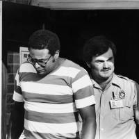 Photo - Capt. Lewis McGee, left, hostage that was released being escorted by a security officer during the Stringtown Riot at the Mack Alford Correctional Center. 5-16-88 by David McDaniel, The Daily Oklahoman ORG XMIT: KOD