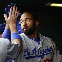Photo -   Los Angeles Dodgers' Matt Kemp, right, high-fives teammate Mark Ellis as he celebrates a first inning home run off a pitch by Colorado Rockies starting pitcher Juan Nicasio during a baseball game Monday, April 30, 2012 in Denver, Colo.. (AP Photo/Barry Gutierrez)