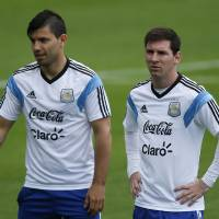 Photo - Argentina's Lionel Messi, right, walks next to teammate Sergio Aguero during a training session in Vespasiano, near Belo Horizonte, Brazil, Thursday, June 12, 2014. Argentina will play in group F of the Brazil 2014 soccer World Cup. (AP Photo/Victor R. Caivano)