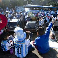 Photo - Fans of Argentina's national soccer team wave to the bus taking the players to the airport in Buenos Aires, Argentina, Monday, June 9, 2014. Argentina's team is leaving Monday to compete in the Brazil's 2014 soccer Word Cup. (AP Photo/Natacha Pisarenko)