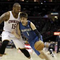Photo - Minnesota Timberwolves' Alexey Shved (1), from Russia, drives past Cleveland Cavalier's Marreese Speights (15) during the second quarter of an NBA basketball game Monday, Feb. 11, 2013, in Cleveland. (AP Photo/Tony Dejak)