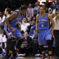 Photo - CELEBRATION: Oklahoma City Thunder's Kevin Durant, left, and Russell Westbrook, right, celebrate following a three-point basket by Westbrook late in the second half of an NBA basketball game against the Dallas Mavericks Wednesday, Feb. 1, 2012, in Dallas. Westbrook had a game-high 33-points in the 95-86 Thunder win. (AP Photo/Tony Gutierrez) ORG XMIT: DNA109