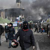 Photo - An anti-government protester walks away during clashes with riot police in Kiev's Independence Square, the epicenter of the country's current unrest, Kiev, Ukraine, Wednesday, Feb. 19, 2014. The deadly clashes in Ukraine's capital have drawn sharp reactions from Washington, generated talk of possible European Union sanctions and led to a Kremlin statement blaming Europe and the West.  (AP Photo/Sergei Chuzavkov)