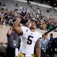 Photo - In this Sept. 15, 2012 photo, Notre Dame linebacker Manti Te'o points to the sky as he leaves the field after a 20-3 win against Michigan State in East Lansing, Mich. In a shocking announcement, Notre Dame said Te'o was duped into an online relationship with a woman whose