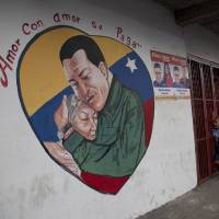 Photo - A heart-shaped mural shows an image of Venezuela's President Hugo Chavez hugging a woman in Caracas, Venezuela, Friday, Jan. 4, 2013. Chavez hasn't spoken publicly or been seen since his Dec. 11 operation in Cuba, and the latest report from his government Thursday night increased speculation that he is unlikely to attend his Jan. 10 inaugural ceremony. The message above the mural reads in Spanish;