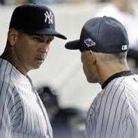 Photo -   New York Yankees' Alex Rodriguez, left, talks to manager Joe Girardi during the 10th inning of Game 3 against the Baltimore Orioles in the American League division baseball series Wednesday, Oct. 10, 2012, in New York. (AP Photo/Kathy Willens)