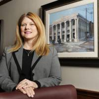 Photo - Suzie Symcox, executive vice president and chief administrative officer of First Fidelity Bank, is shown Tuesday in the board room at First Fidelity Bank headquarters in Oklahoma City. The painting is First Fidelity's first bank in Norman shown as it appeared in August of 1920. Photo by Paul B. Southerland, The Oklahoman  PAUL B. SOUTHERLAND