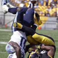 Photo - Pittsburgh Steelers running back Isaac Redman (33) is hit by Tennessee Titans strong safety Bernard Pollard (31) in the fourth quarter of an NFL football game in Pittsburgh, Sunday, Sept. 8, 2013. (AP Photo/Gene J. Puskar)