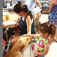 Photo - A large yellow Labrador retriever mix basks in the attention of Olivia Parker, 3, as her mother, Tracy Parker, completes the necessary paperwork to adopt the dog and take it home. PHOTO BY LYNETTE LOBBAN, FOR THE OKLAHOMAN