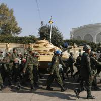 Photo - Soldiers walk past a military tank securing the presidential palace in Cairo, Egypt, Thursday, Dec. 13, 2012. Egypt's opposition called on its followers to vote