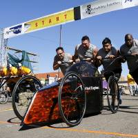 Photo - A car sponsored by United Engines leaves the starting line during the Rebuilding Together OKC Construction Derby on Sunday.  Photo by Jim Beckel,  The Oklahoman  Jim Beckel - THE OKLAHOMAN