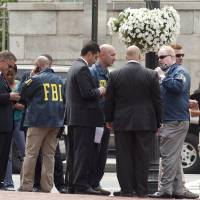 Photo -   Washington Police and FBI agents gather outside the Family Research Council in Washington, Wednesday, Aug. 15, 2012, after security guard at the lobbying group was been shot in the arm. A police spokeswoman says the shooting happened Wednesday morning at the Family Research Council. Police say one person has been taken into custody. (AP Photo/J. Scott Applewhite)