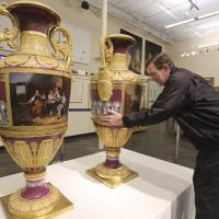 Photo - In this photo made Thursday, April 4, 2013, Jerry Holley, executive vice president of Dallas Auction Gallery, rotates a rare Russian vases made in 1833 by Russia's Imperial Porcelain Factory and on display at the gallery in Dallas. The rare 4 1/2-foot tall vases, which had been packs away for around a decade, were sold Thursday, April 11, 2013, for $2.7 million in a private sale about a week before they were to be auctioned. (AP Photo/LM Otero)