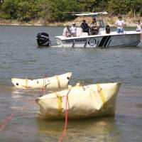 Photo - A boat pops up to the surface as the Oklahoma Highway Patrol Dive Team spends the day floating a submerged boat and car from the bottom of Lake Tenkiller near Gore, OK, as part of ongoing training exercises, Tuesday, May 6, 2014,  Photo by Paul Hellstern, The Oklahoman