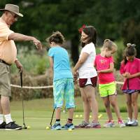 Photo -  Volunteer Henry Drury gives putting lessons during a free junior golf clinic at Westwood Golf Course. PHOTO BY STEVE SISNEY, THE OKLAHOMAN   STEVE SISNEY -