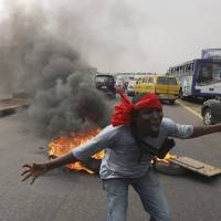 Photo - FILE- An unidentified man shouts slogans near burning tyres during a protest on a major road junction in the commercial capital of Lagos, Nigeria, during a fuel subsidy protest in this file photo dated Tuesday, Jan. 3, 2012, as angry mobs call on the government to keep a cherished consumer subsidy that had kept gas affordable for more than two decades. A 30-minute film documentary called