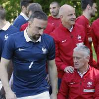 Photo - France's forward Franck Ribery, left, walks out as France's assistant coach Guy Stephan, right,  holds the shoulder of head coach Didier Deschamps, bottom right, after the team picture at the French national football team's training base, in Clairefontaine, outside Paris, Friday, June 6, 2014 as part of France's national football team's preparation for the upcoming FIFA 2014 World Cup in Brazil. (AP Photo/Francois Mori)
