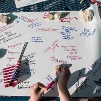 Photo - Active members of the military, veterans and civilians sign posters at Lions Club Park that will be delivered to the families of the victims affected by the Fort Hood shooting tragedy, on Friday, April 4, 2014, in Killeen, Texas. On April 2, three people were killed and 16 were wounded when a gunman opened fire before taking his own life at the Fort Hood military base. (AP Photo/Tamir Kalifa)