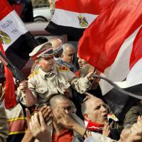 Photo - Egyptian pro-military supporters carry Yousef Mohammed, 7, as he wears a representation of a military uniform during a protest in Cairo, Egypt, Friday, March 1, 2013. Hundreds of pro-military supporters gathered to reject the Muslim Brotherhood and President Mohammed Morsi's rule calling for the military to return to power.  (AP Photo/Amr Nabil)