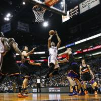 Photo - Oklahoma City Thunder's Thabo Sefolosha (2), of Switzerland, shoots as he gets past Phoenix Suns' Luis Scola, third from left, of Argentina, and Marcin Gortat, third from right, of Poland, while Thunder's Kendrick Perkins (5) and Kevin Durant (35) watch along with Suns' Goran Dragic (1), of Slovenia, during the first half in an NBA basketball game, Sunday, Feb. 10, 2013, in Phoenix. (AP Photo/Ross D. Franklin)