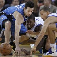Photo - Orlando Magic guard J.J. Redick, left, reaches for a loose ball next to Golden State Warriors center Festus Ezeli, center, and guard Stephen Curry during the first quarter of an NBA basketball game in Oakland, Calif., Monday, Dec. 3, 2012. (AP Photo/Jeff Chiu)