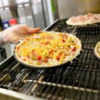 Photo - An employee puts a pizza into the oven  at the Hideaway Pizza restaurant on Northwest Expressway in northwest Oklahoma City on Tuesday, March 3, 2009. By John Clanton, The Oklahoman ORG XMIT: KOD