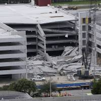 Photo -   A five-story parking garage is shown after it collapsed at Miami-Dade College, Wednesday, Oct. 10, 2012 in Doral, Fla., killing one worker and trapping two others in the rubble, officials said. Several other workers were hurt, including one rescued from the debris. (AP Photo/Lynne Sladky)