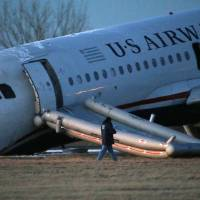 Photo - A person walks around a damaged US Airways jet at the end of a runway at the Philadelphia International Airport, Thursday, March 13, 2014, in Philadelphia. Airline officials said the flight was heading to Fort Lauderdale, Fla., when the pilot was forced to abort takeoff around 6:30 p.m., after the front landing gear failed. An airport spokeswoman said no injuries have been reported. (AP Photo/Matt Slocum)
