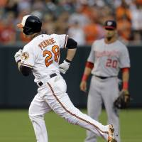 Photo - Baltimore Orioles' Steve Pearce rounds the bases past Washington Nationals shortstop Ian Desmond after hitting a solo home run in the first inning of an interleague baseball game, Thursday, July 10, 2014, in Baltimore. (AP Photo/Patrick Semansky)