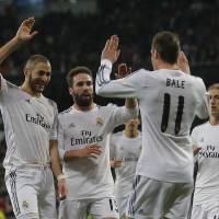 Photo - Real Madrid's Karim Benzema from France, left, celebrates his goal with Real Madrid's Gareth Bale from Great Britain, second right, and teammates during a Spanish La Liga soccer match between Real Madrid and Villarreal at the Bernabeu stadium stadium in Madrid, Spain, Saturday, Feb. 8, 2014. (AP Photo/Andres Kudacki)