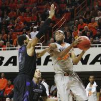 Photo - Oklahoma State's Markel Brown (22) attempts to jump by Kansas State defender Shane Southwell, left, during an NCAA college basketball game in Stillwater, Okla., Monday, March 3, 2014. Oklahoma State won 77-61. (AP Photo/The Oklahoman, KT King)