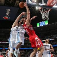 Photo - Houston Rockets forward Donatas Motiejunas, third from left, of Lithuania, is fouled as he goes up for a shot by Denver Nuggets guard Aaron Brooks, second from left, and center Timoey Mozgov, of Russia, left, as guard Randy Foye, right, looks on in the first quarter of an NBA basketball game in Denver on Wednesday, April 9, 2014. (AP Photo/David Zalubowski)