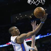 Photo - Oklahoma City Thunder guard Russell Westbrook (0) shoots in front of San Antonio Spurs guard Nando De Colo (25) in the second quarter of an NBA basketball game in Oklahoma City, Monday, Dec. 17, 2012. (AP Photo/Sue Ogrocki)