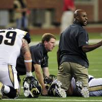 Photo -   St. Louis Rams guard Robert Turner (59) kneels as team officials help tackle Rodger Saffold after he sustained an injury during the fourth quarter of an NFL football game against the Detroit Lions in Detroit, Sunday, Sept. 9, 2012. (AP Photo/Carlos Osorio)