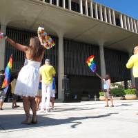 Photo - Gay marriage supporters rally outside the Hawaii Capitol in Honolulu ahead of a Senate vote on whether to legalize same-sex marriage on Tuesday, Nov. 12, 2013. (AP Photo/Oskar Garcia)