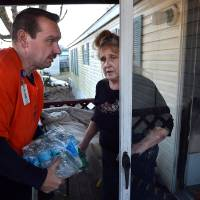 Photo - JoAnn Chapouris asks Paramedic John Johnson to carry a case of water inside her home in Rand, W.Va. Sunday Jan. 12, 2014.  The water emergency continues in the Charleston area due to a chemical spill.  (AP Photo/Charleston Daily Mail, Craig Cunningham)